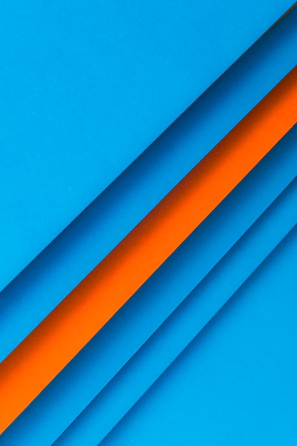 Arranged striped blue and an orange paper backdrop Free Photo