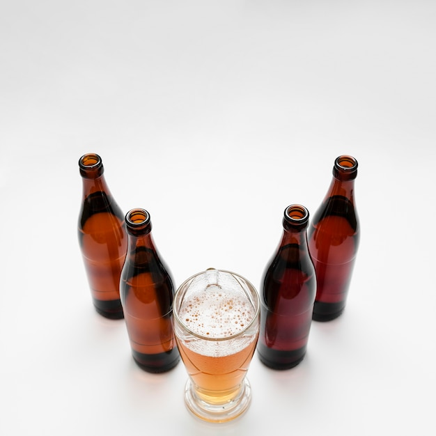Arrangement of beer bottles with glass Free Photo