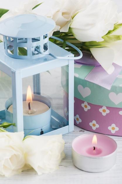 Arrangement of blue lanter, flowers, pastel gift box Premium Photo