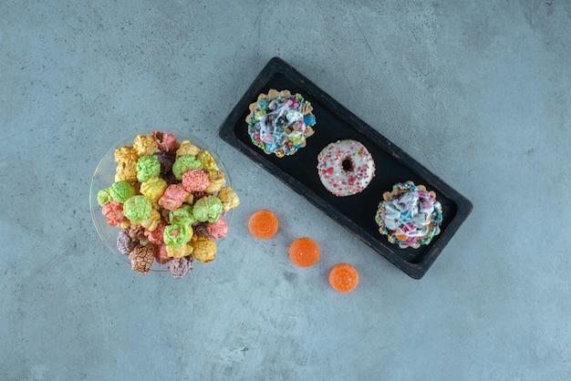 Disposizione di snack canditi con ciambelle, popcorn, cupcakes e caramelle di gelatina sulla superficie di marmo Foto Gratuite