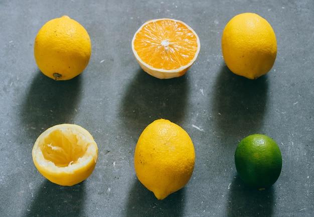 An arrangement of citrus fruits, lemons, orange and limes on a gray background. Premium Photo
