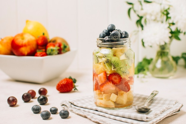Arrangement of colorful fruits in a jar Free Photo