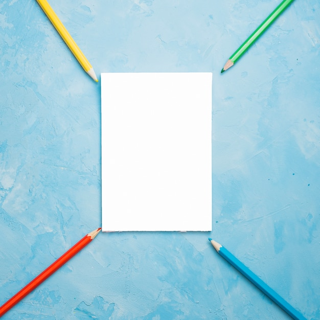 Arrangement of colorful pencil with white blank card on blue textured surface Free Photo