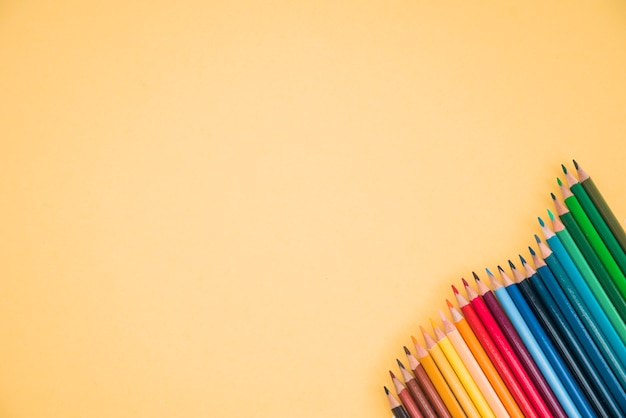 Arrangement of colorful pencils at the corner of yellow backdrop Free Photo