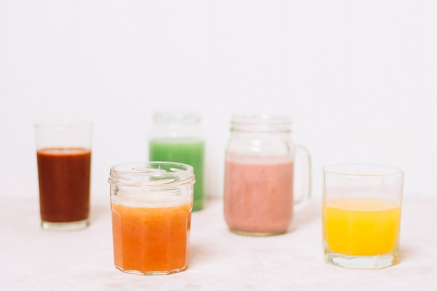 Arrangement of colorful smoothies with white background Free Photo
