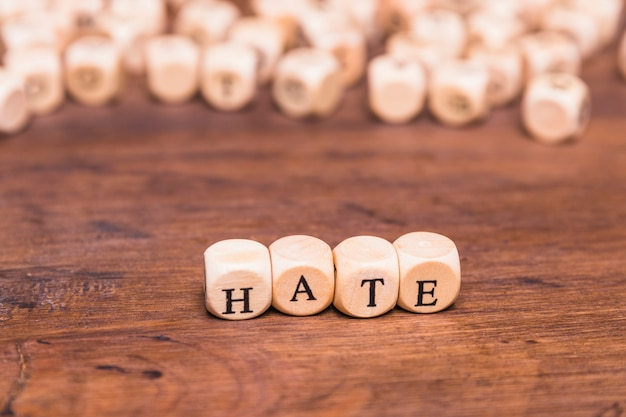 Arrangement of cubes with text hate on wooden table Free Photo