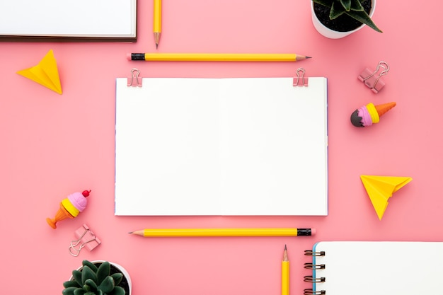 Arrangement of desk elements on pink background with empty notebook Free Photo
