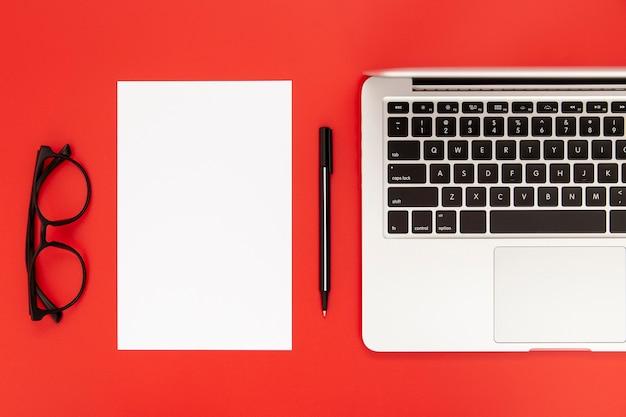 Arrangement of desk elements on red background Free Photo