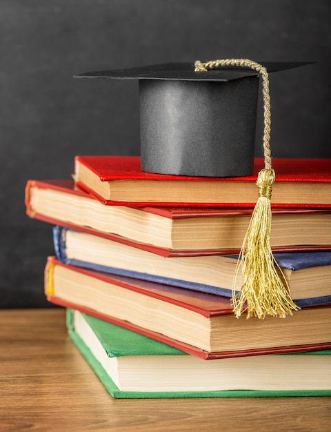 Arrangement of different books with a graduation cap Premium Photo