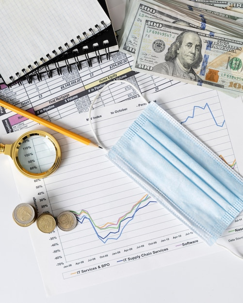 Arrangement of finances elements and graph with medical mask Free Photo
