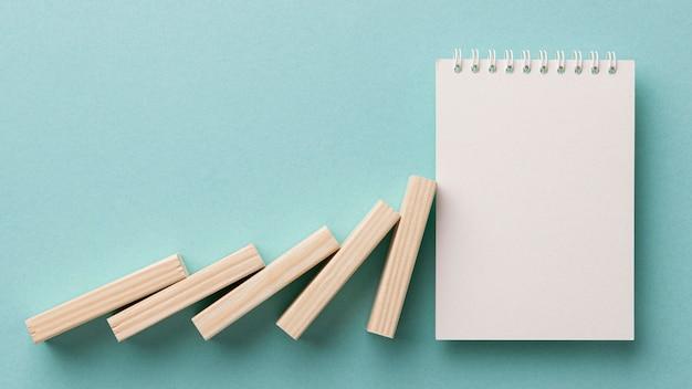 Disposizione della crisi finanziaria con pezzi di legno sul blocco note in bianco Foto Gratuite