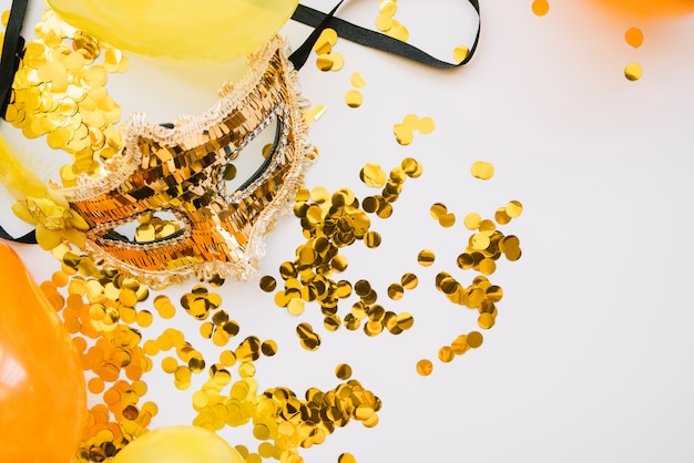 Arrangement of golden mask and confetti Free Photo