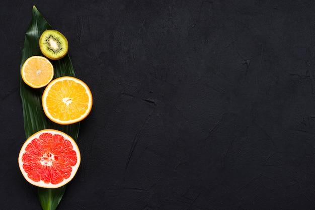 Arrangement of half of tropical fruits on banana leaf on black background Free Photo