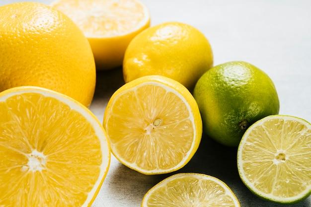 Arrangement of lemons and limes on plain background Free Photo