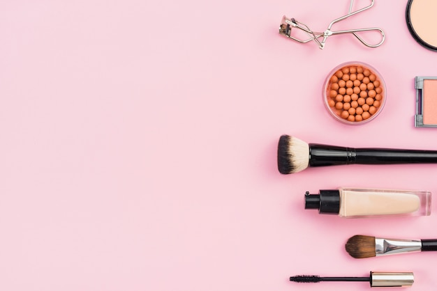 Arrangement of makeup products on pink background Free Photo
