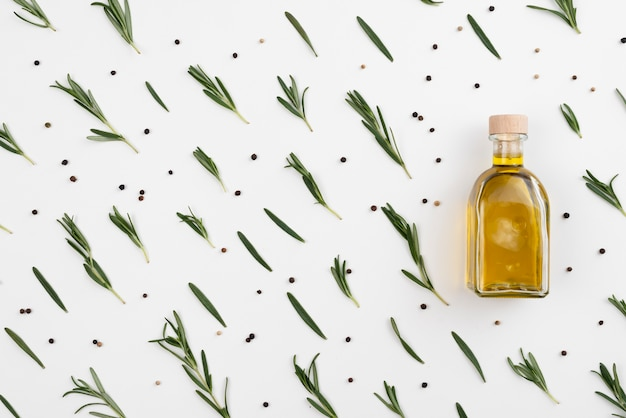 Arrangement of olive leaves with oil in bottle Free Photo
