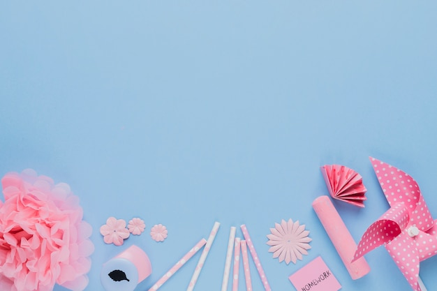 Arrangement of pink craft art and equipment on blue backdrop Free Photo