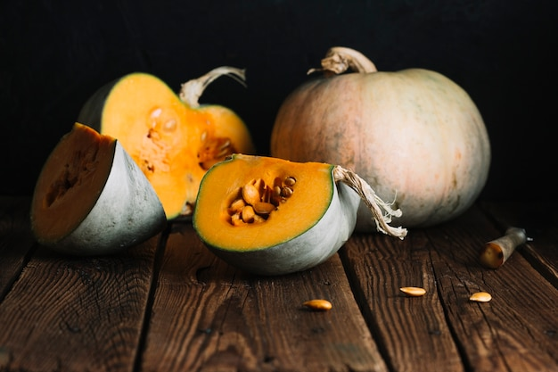 Arrangement of pumpkins and slices on wooden background Free Photo