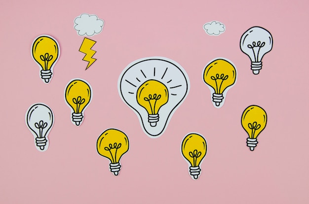Arrangement of silver and golden light bulbs on pink background Free Photo