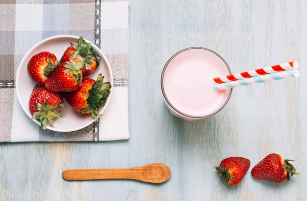 Arrangement of strawberries and smoothie with straws Free Photo