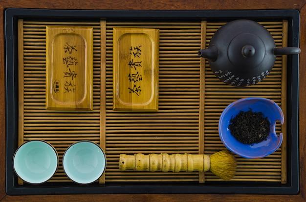 An arrangement of a tea pot; cups; brush; herbs on wooden tray Free Photo