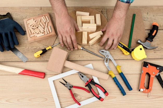 Arrangement of tools and worker hands carpentry concept Free Photo
