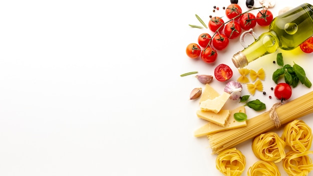 Arrangement of uncooked pasta and ingredients with copy space Free Photo