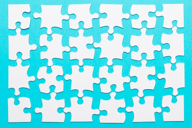 Arrangement of white puzzle piece over blue background Free Photo