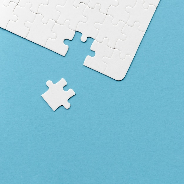Arrangement of white puzzle pieces for individuality concept on blue background Free Photo