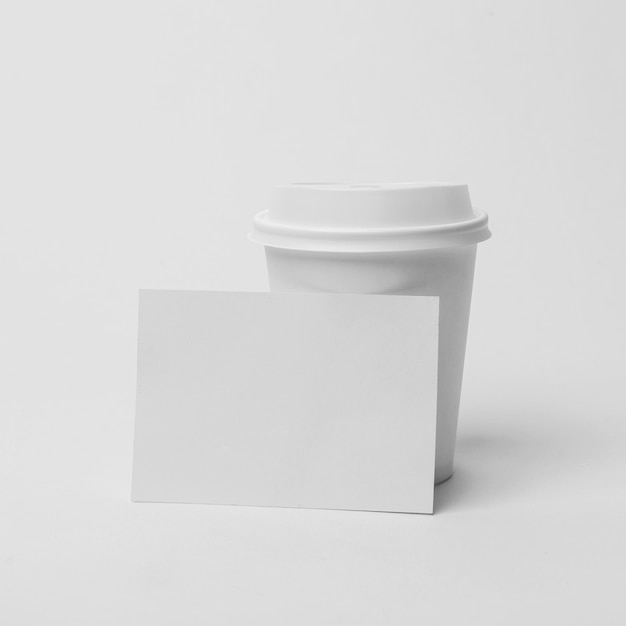 Arrangement with coffee cup and paper piece Free Photo