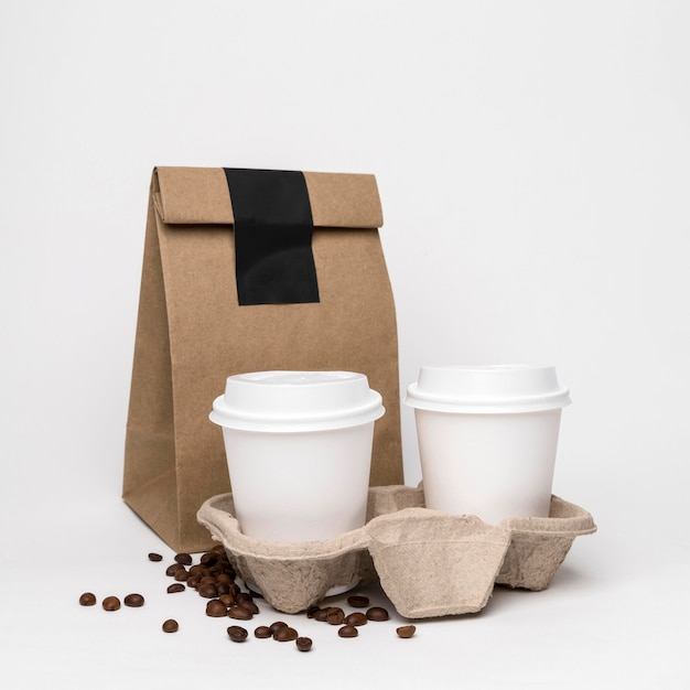 Arrangement with coffee cups and paper bag Free Photo