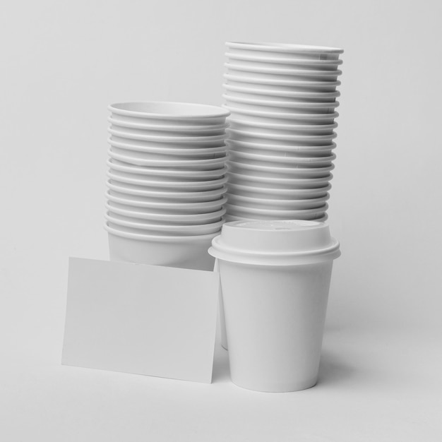Arrangement with coffee cups and paper piece Free Photo