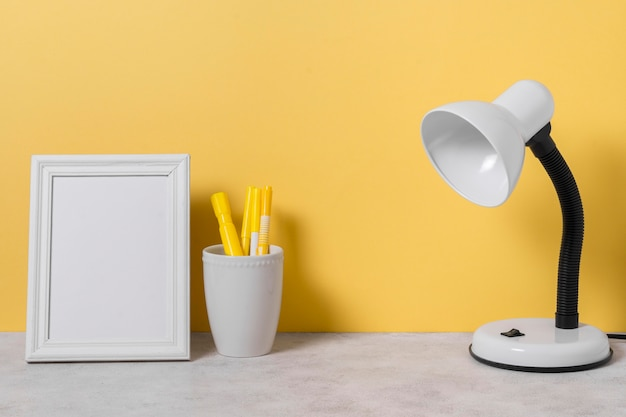 Arrangement with desk lamp and pens Free Photo