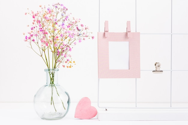 Arrangement with frame and flower vase Free Photo