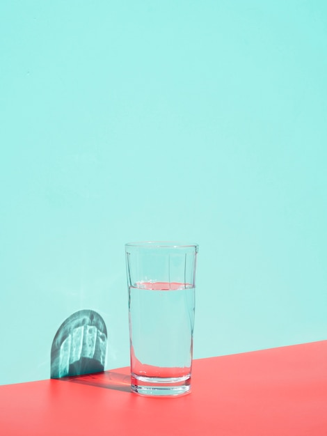 Arrangement with glass of water near blue wall Free Photo