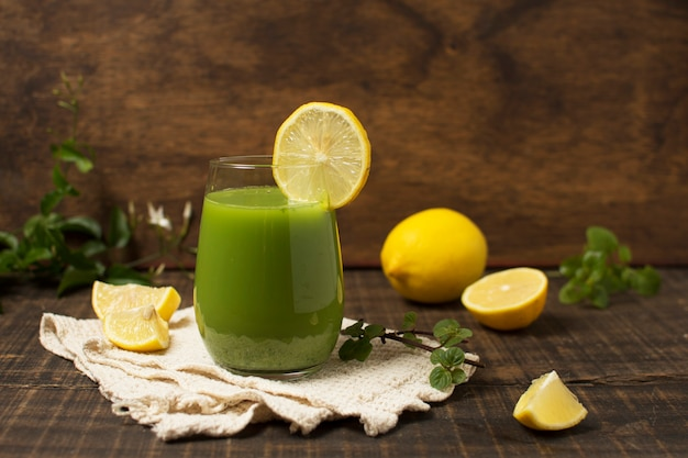 Arrangement with green smoothie and lemons Free Photo