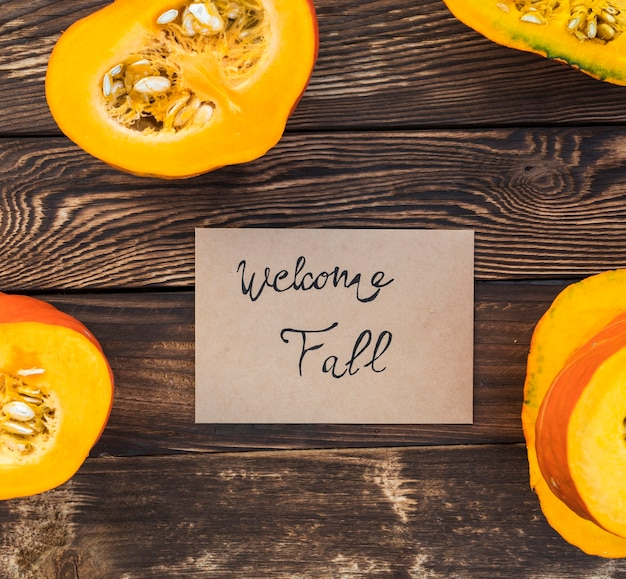 Arrangement with greeting card and cut pumpkin Free Photo