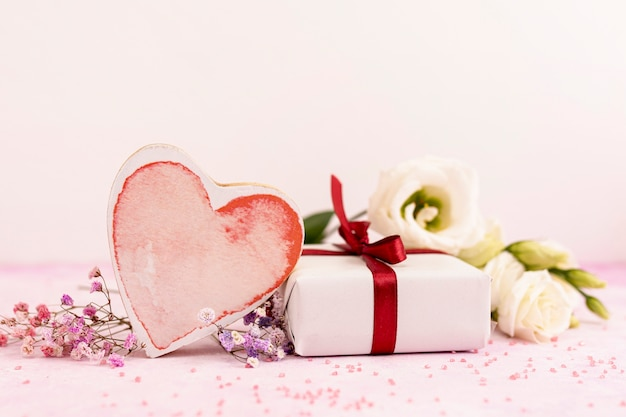 Arrangement with heart shaped cookie and present Free Photo