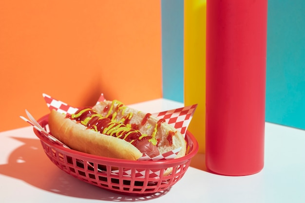 Arrangement with hot dog in basket and sauce bottles Free Photo