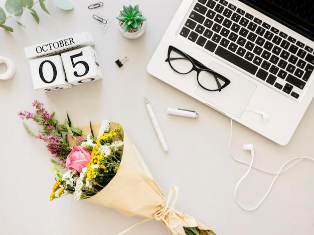 Disposizione con laptop e fiori Foto Gratuite