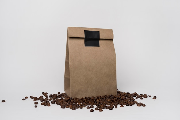 Arrangement with paper bag on coffee beans Free Photo