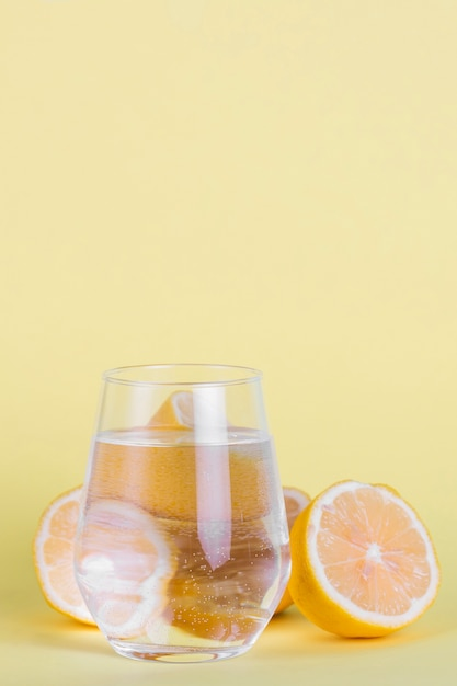 Arrangement with small glass of water and lemons Free Photo