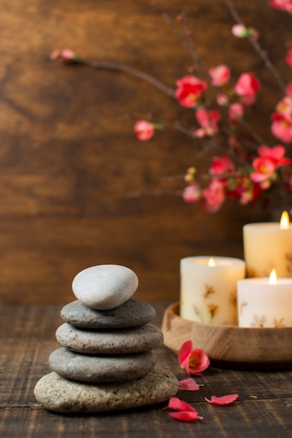 Arrangement with spa stones and lit candles Free Photo