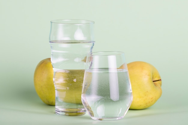 Arrangement with water and yellow apples Free Photo