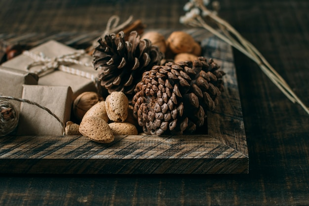 Arrangement with wooden frame and cones Free Photo