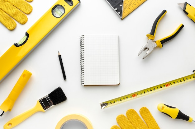 Arrangement of yellow repair tools and notepad Free Photo