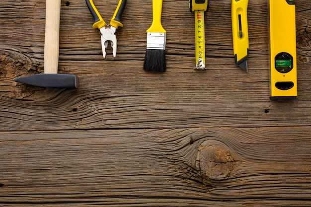 Arrangement of yellow repair tools on wooden background Free Photo