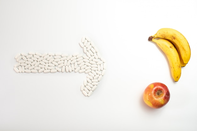 Arrow with pills pointing a fruit against supplements, concept of healthy nutrition. Premium Photo