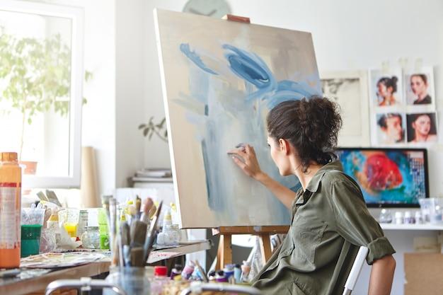 Концепция искусства, творчества, хобби, работы и творчества. вид сзади занятой художницы, сидящей на стуле перед мольбертом, рисующей пальцами, используя бело-синюю масляную или акриловую краску Бесплатные Фотографии