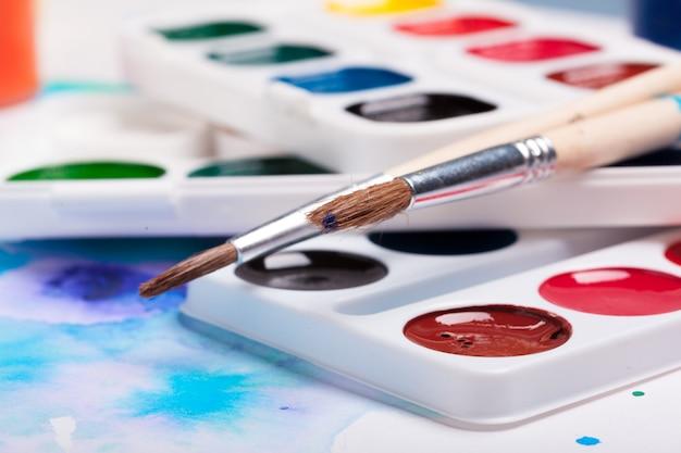 Art palette with colorful paints close up top view Premium Photo